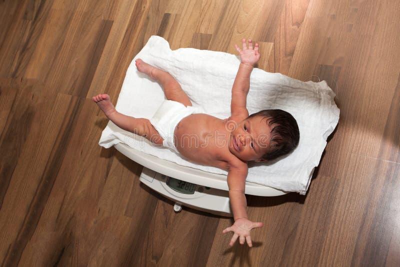 Pesaje de un bebé recién nacido fotos de archivo libres de regalías