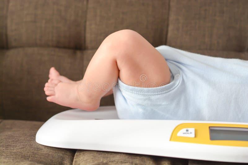Pesaje del bebé en escala imagen de archivo libre de regalías