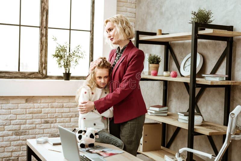 Pesar de la mujer adulta en la chaqueta roja que abraza a su hija ofendida imágenes de archivo libres de regalías