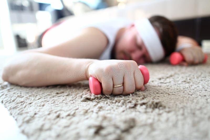 Pesas de gimnasia agotadas del sueño y del control del hombre en manos imagen de archivo libre de regalías