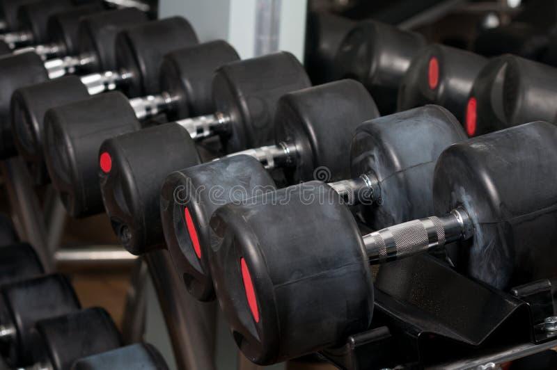 Pesas de gimnasia alineadas en un centro de aptitud fotografía de archivo