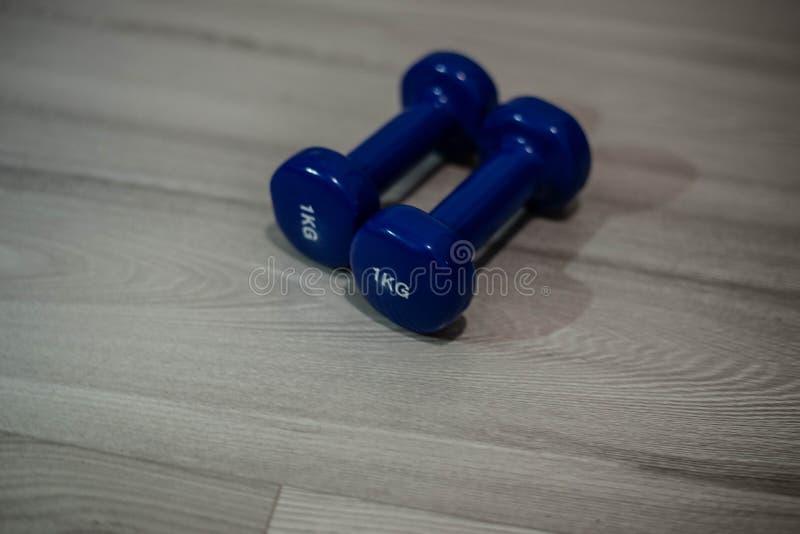 Pesas de gimnasia azules en el piso foto de archivo