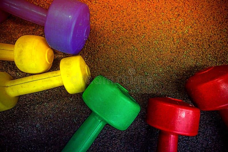 Pesas de gimnasia coloreadas en un fondo negro imagen de archivo