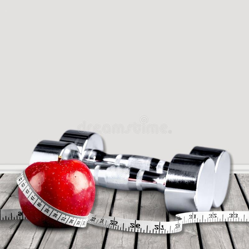 Pesas de gimnasia con la cinta métrica y la manzana para la dieta imagen de archivo libre de regalías