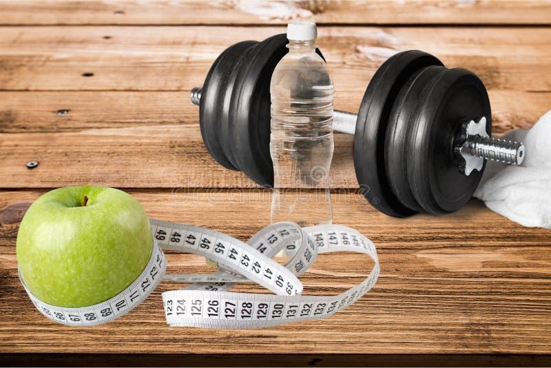 Pesas de gimnasia con la cinta métrica y la manzana para la dieta imágenes de archivo libres de regalías