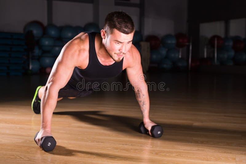 Pesas de gimnasia de Doing Pushups With del atleta del hombre joven como parte del entrenamiento del levantamiento de pesas fotos de archivo libres de regalías