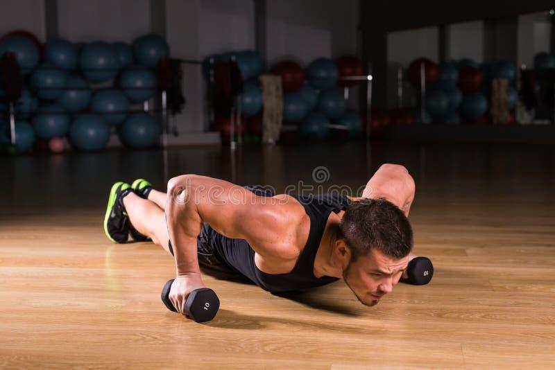 Pesas de gimnasia de Doing Pushups With del atleta del hombre joven como parte del entrenamiento del levantamiento de pesas imagen de archivo