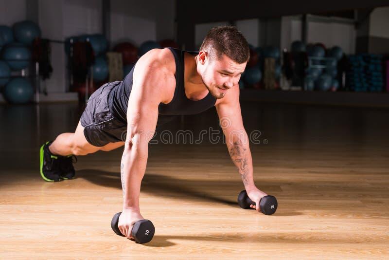 Pesas de gimnasia de Doing Pushups With del atleta del hombre joven como parte del entrenamiento del levantamiento de pesas fotos de archivo