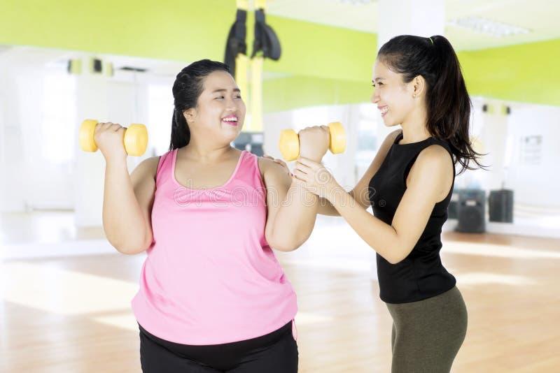Pesas de gimnasia de elevación de la mujer gorda con su instructor personal fotografía de archivo libre de regalías