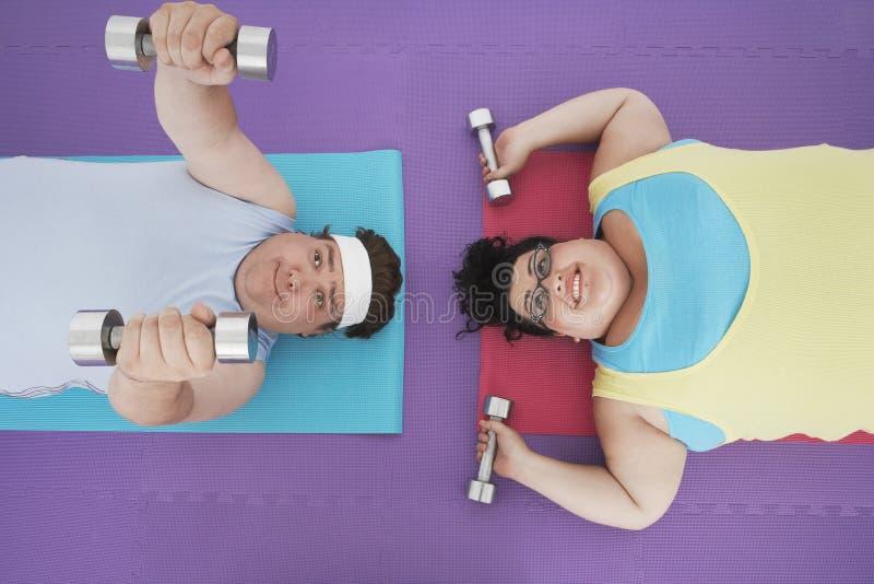 Pesas de gimnasia de elevación de los pares gordos fotografía de archivo