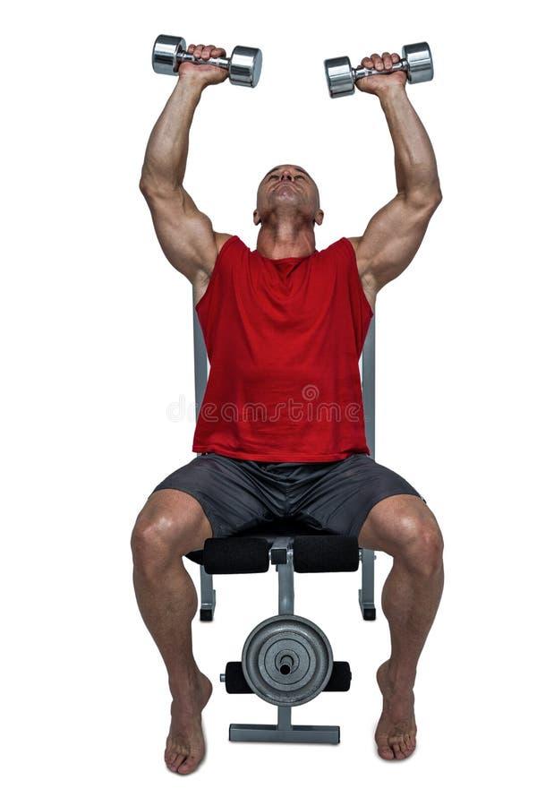 Pesas de gimnasia de elevación del hombre sano mientras que se sienta en la prensa de banco imágenes de archivo libres de regalías