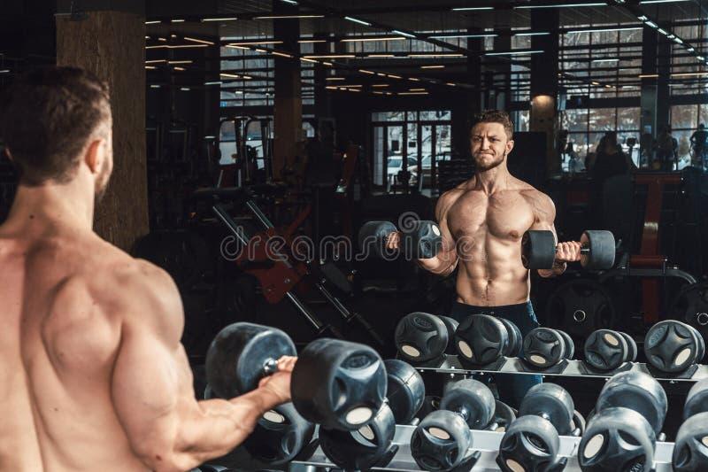 Pesas de gimnasia de elevación apuestas del hombre joven y trabajo en su bíceps delante del espejo en el gimnasio fotografía de archivo libre de regalías