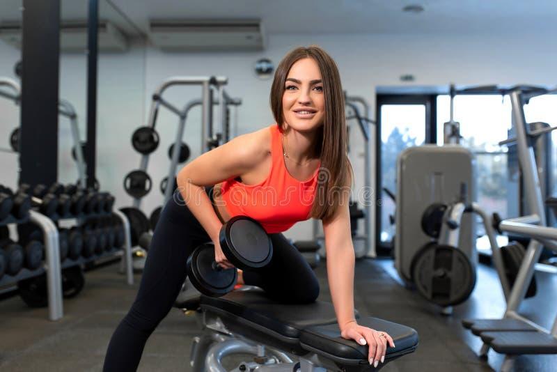 Pesas de gimnasia de elevación de la mujer apta hermosa del retrato en banco en el gimnasio fotos de archivo