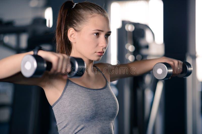 Pesas de gimnasia de elevaci?n de la mujer joven atractiva de los deportes en el gimnasio Aptitud y forma de vida sana fotografía de archivo libre de regalías