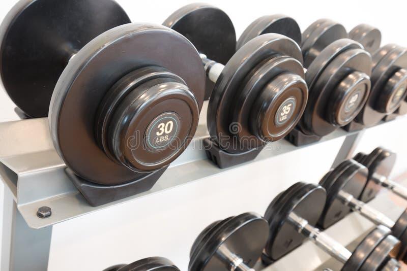 Pesas de gimnasia en un estante fotografía de archivo