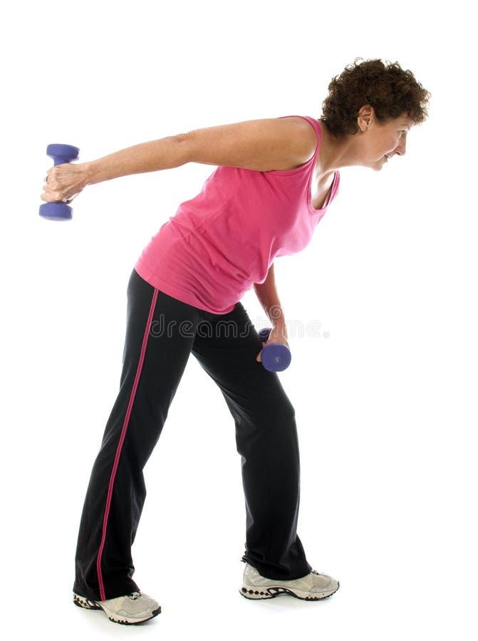 Pesas de gimnasia mayores del ejercicio del atleta de la mujer de la Edad Media imagen de archivo