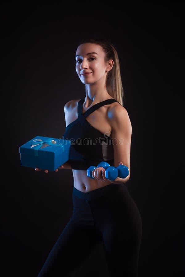Pesas de gimnasia que se sostienen rubias atléticas y caja de regalo en sus manos imagen de archivo