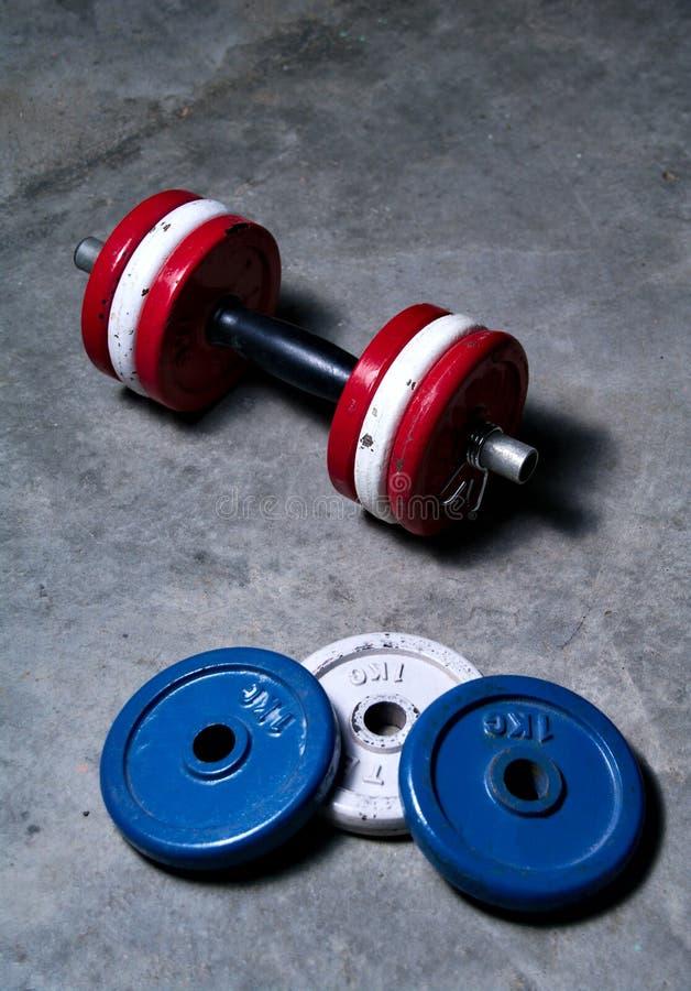 Pesas de gimnasia rojo, blanco y azul en fondo concreto imagenes de archivo