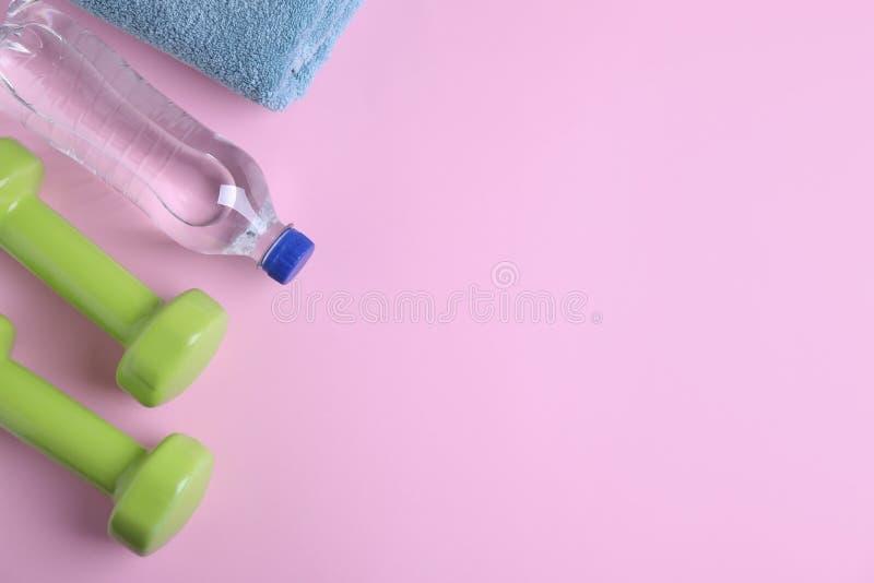 Pesas de gimnasia, toalla y botella del vinilo de agua en el fondo del color, endecha plana imágenes de archivo libres de regalías