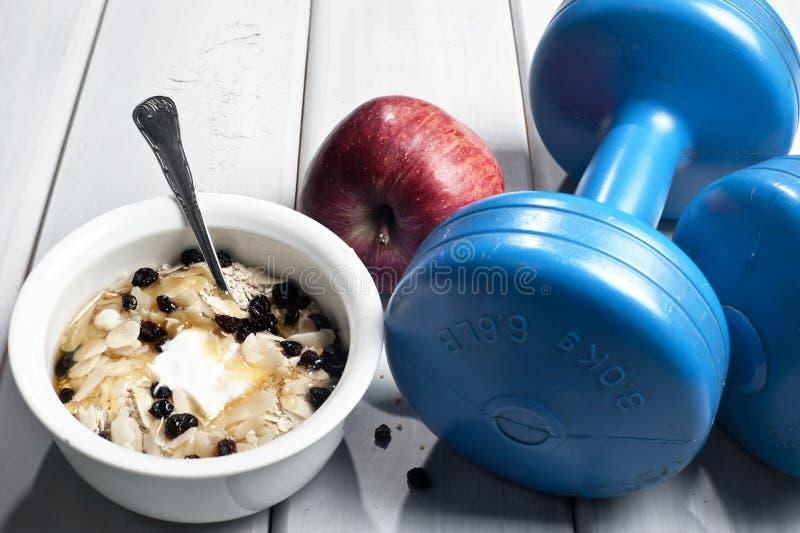 Pesas de gimnasia y cuenco con el yogur imágenes de archivo libres de regalías