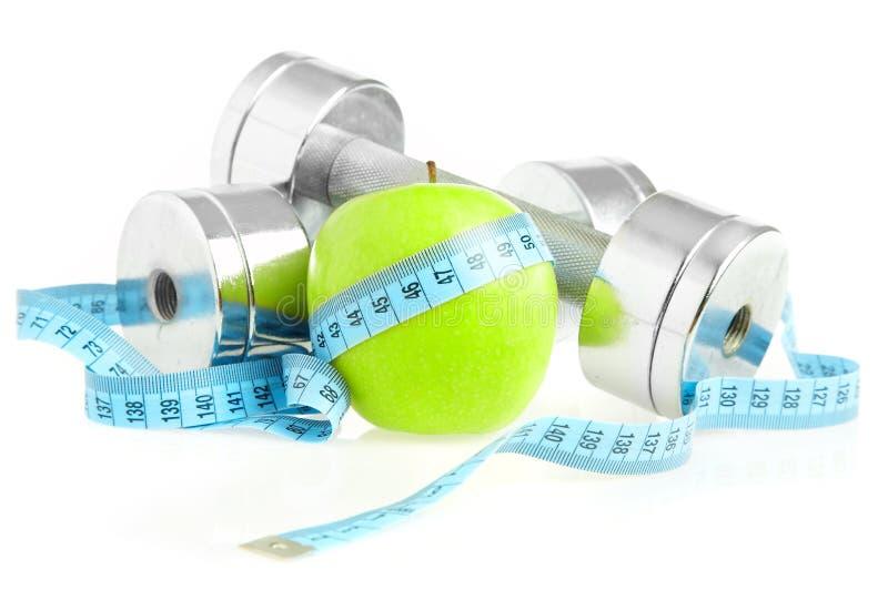 Pesas de gimnasia y manzana. foto de archivo libre de regalías