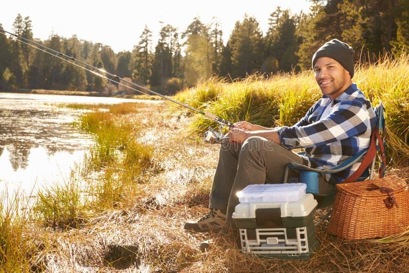Pesca afro-americano do homem pelo lago fotografia de stock royalty free