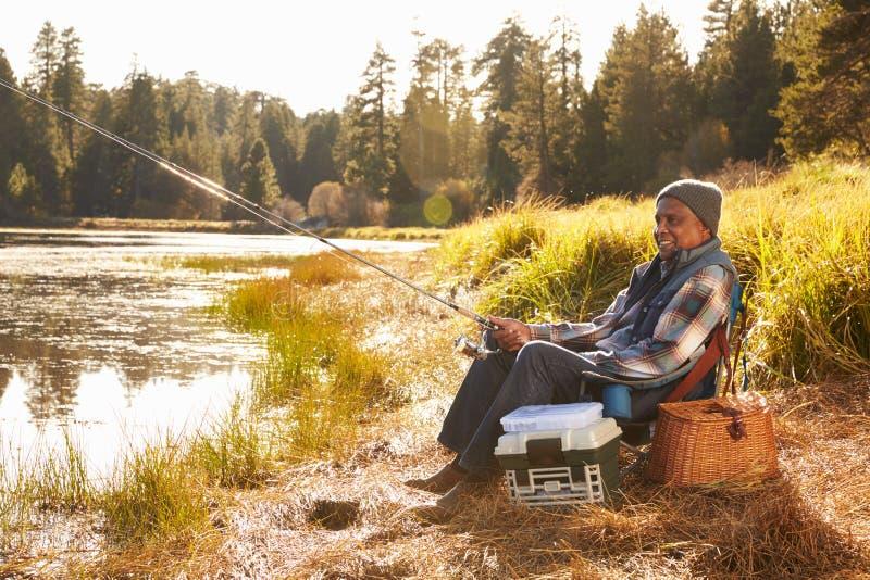 Pesca afroamericana mayor del hombre por el lago fotografía de archivo