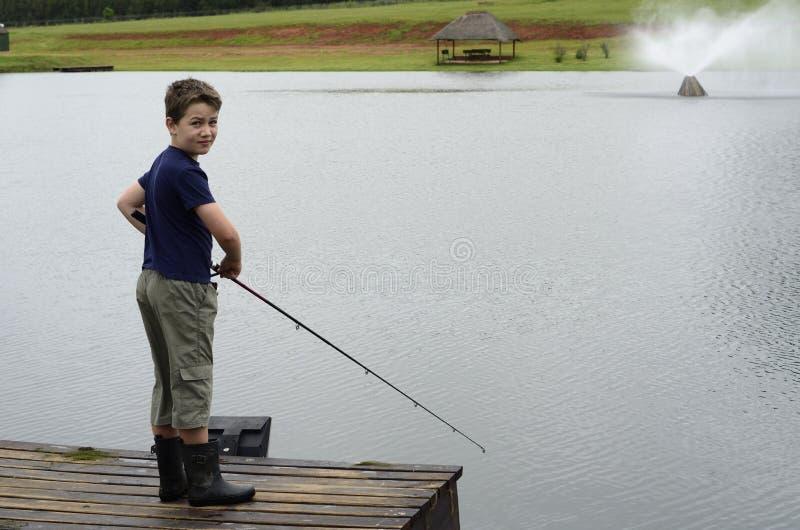 Pesca bassa del ragazzo sulla diga o sul pilastro del lago fotografie stock