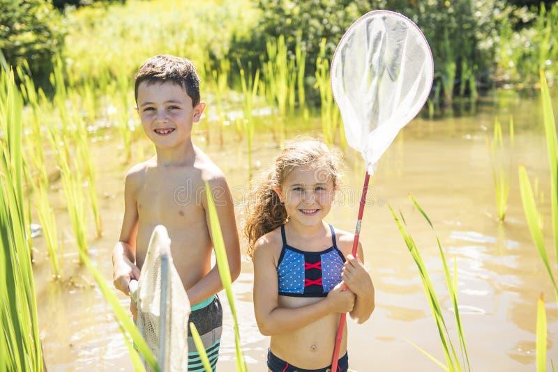 Pesca bonito da menina e do menino com uma rede em um lago imagens de stock royalty free
