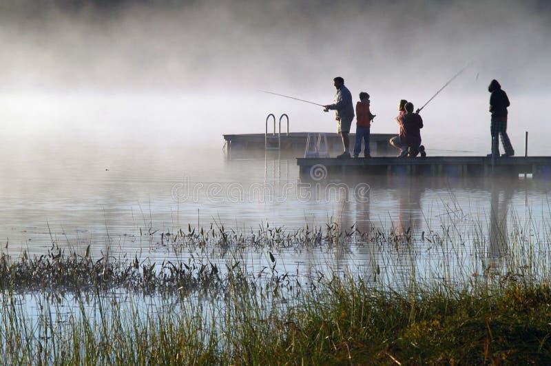Pesca brumosa de la salida del sol en el lago fotos de archivo libres de regalías