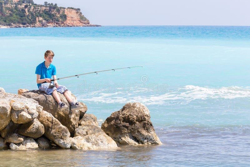 Pesca caucasica dell'adolescente con la barretta vicino al mare ed alla spiaggia immagini stock