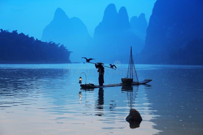 Pesca cinese dell'uomo con gli uccelli dei cormorani fotografie stock libere da diritti