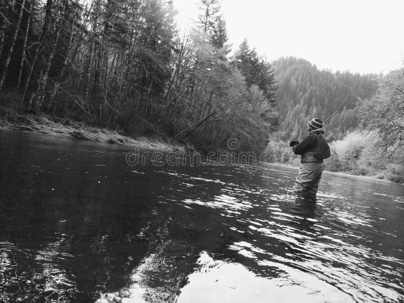 Pesca com mosca do homem no tempo frio do inverno fotografia de stock