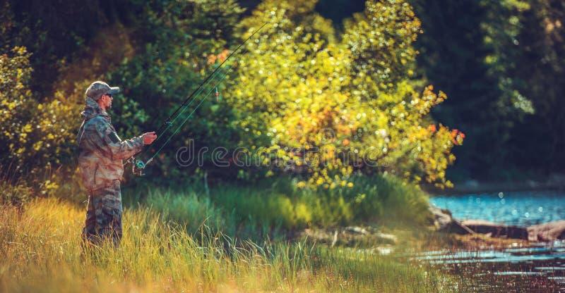 Pesca com mosca dos homens em um rio imagens de stock