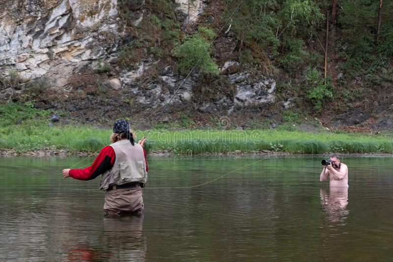 Pesca com mosca e fotógrafo despido no rio reportage Photosession na natureza Paisagem da montanha fotos de stock