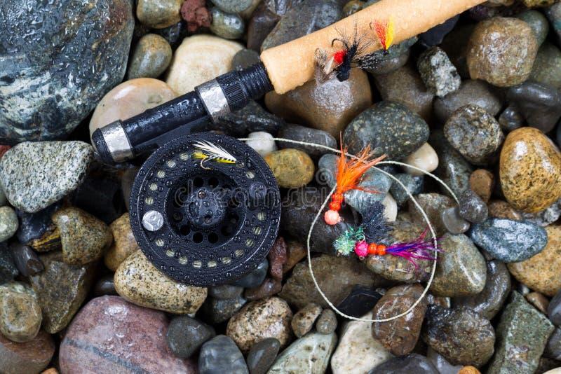 Pesca com mosca polo e carretel com as moscas em pedras molhadas foto de stock royalty free