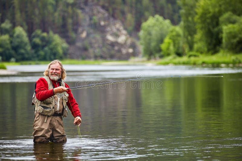 Pesca con la mosca in fiume durante l'ecoturismo fotografia stock