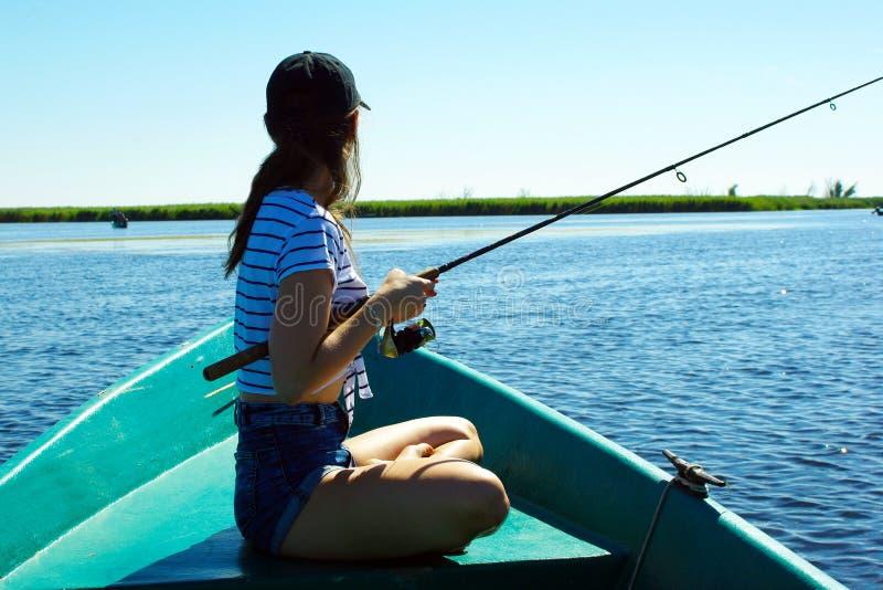 Pesca da menina de um barco fotos de stock royalty free