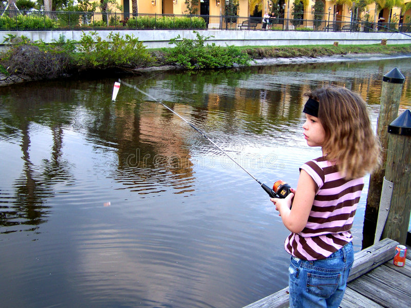 Pesca da menina fora da doca imagem de stock