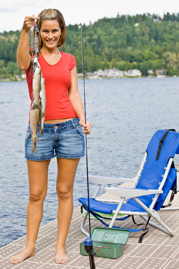 Pesca da mulher no cais imagem de stock