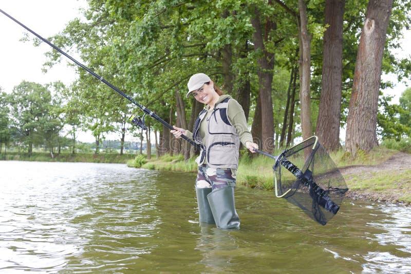 Pesca da mulher no rio na mola fotografia de stock