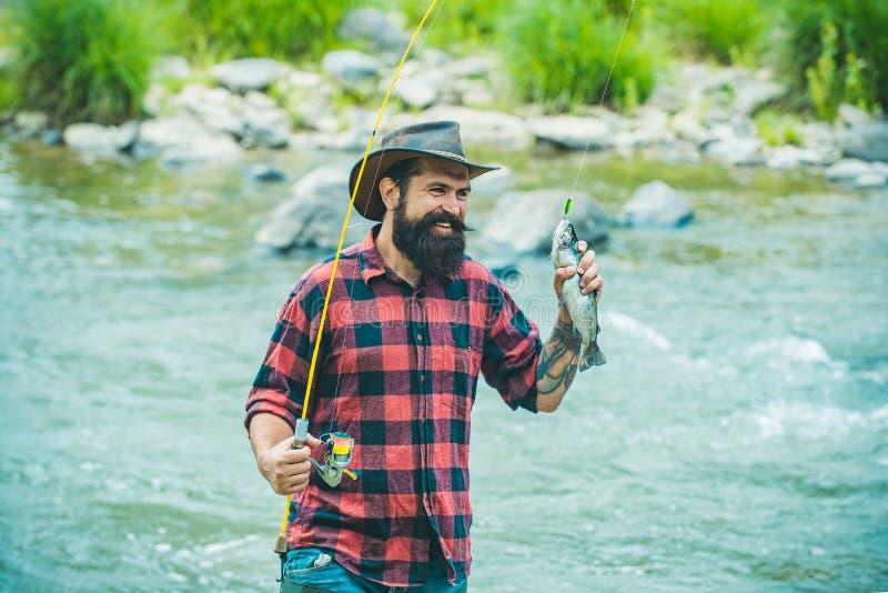 Pesca da perda Truta do pescador e do troféu Timalo do rio no gancho Pesca desportiva Método para travar a truta pesca foto de stock royalty free