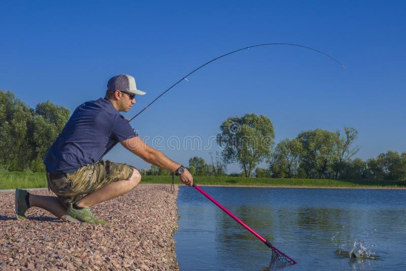 Pesca da truta da ?rea Pescador com a haste de giro na a??o que joga peixes fotos de stock royalty free