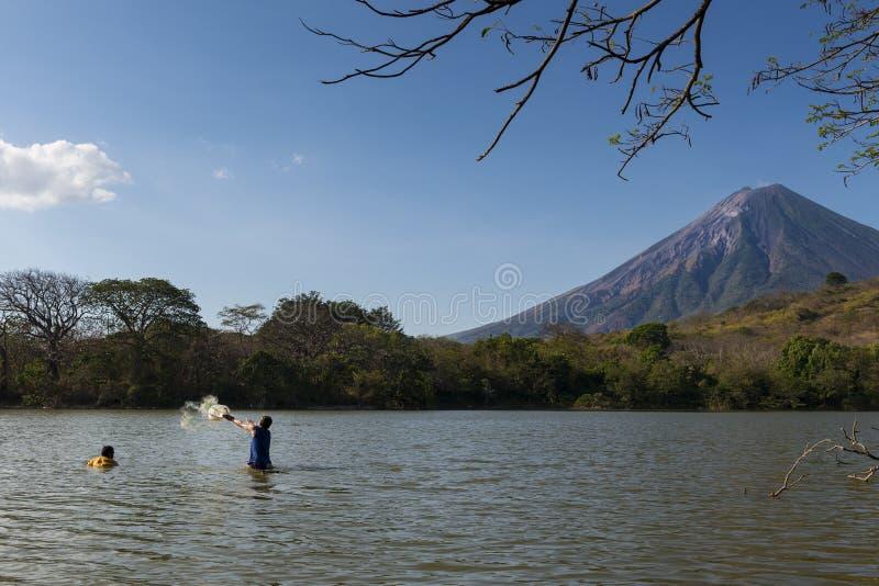Pesca de dos pescadores en las orillas de la isla de Ometepe en el lago Nicaragua, con el volcán de Concepción en el fondo fotografía de archivo libre de regalías