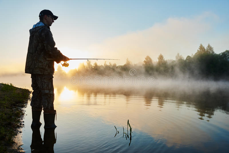 Pesca de Fisher no nascer do sol nevoento fotos de stock