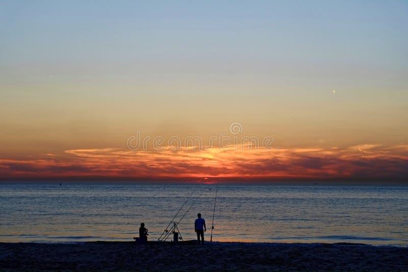 Pesca de la costa en la playa por puesta del sol imágenes de archivo libres de regalías
