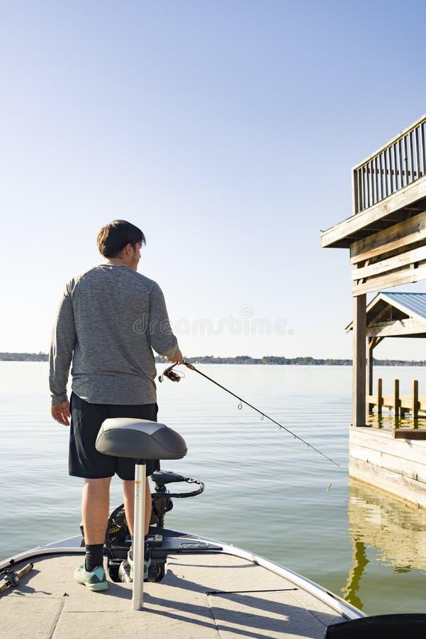 Pesca de la lubina en barco bajo en el lago fotografía de archivo