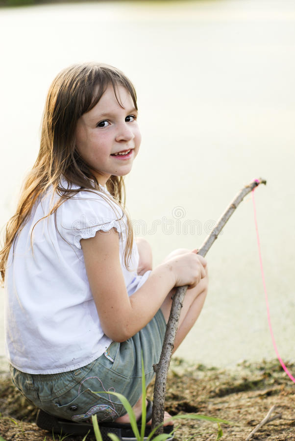 Pesca de la muchacha con un palillo y una línea imagen de archivo libre de regalías