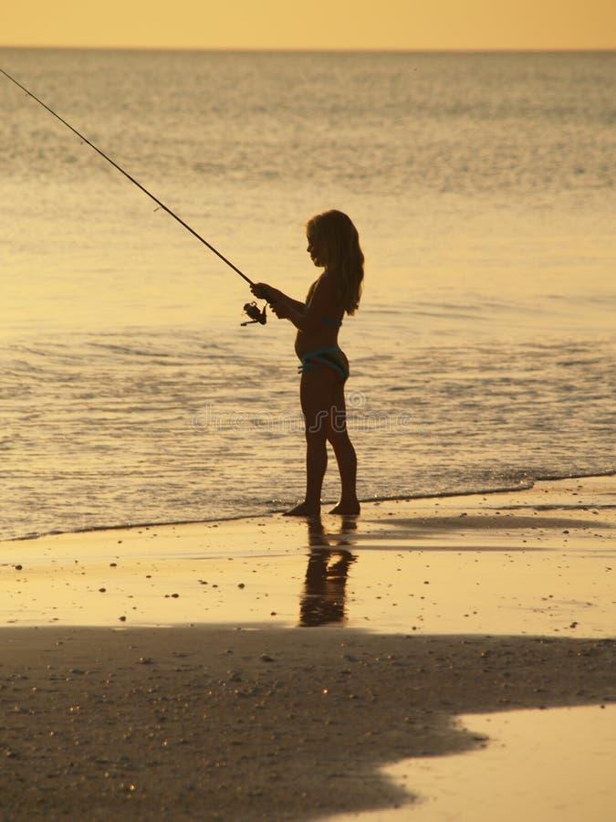 Pesca de la muchacha en la playa de la puesta del sol fotos de archivo
