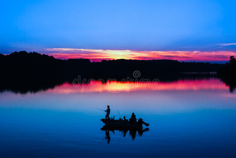 Pesca de lago en la puesta del sol imagen de archivo